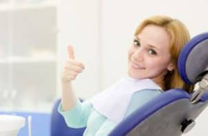 Woman sitting in a dental chair giving a thumbs up